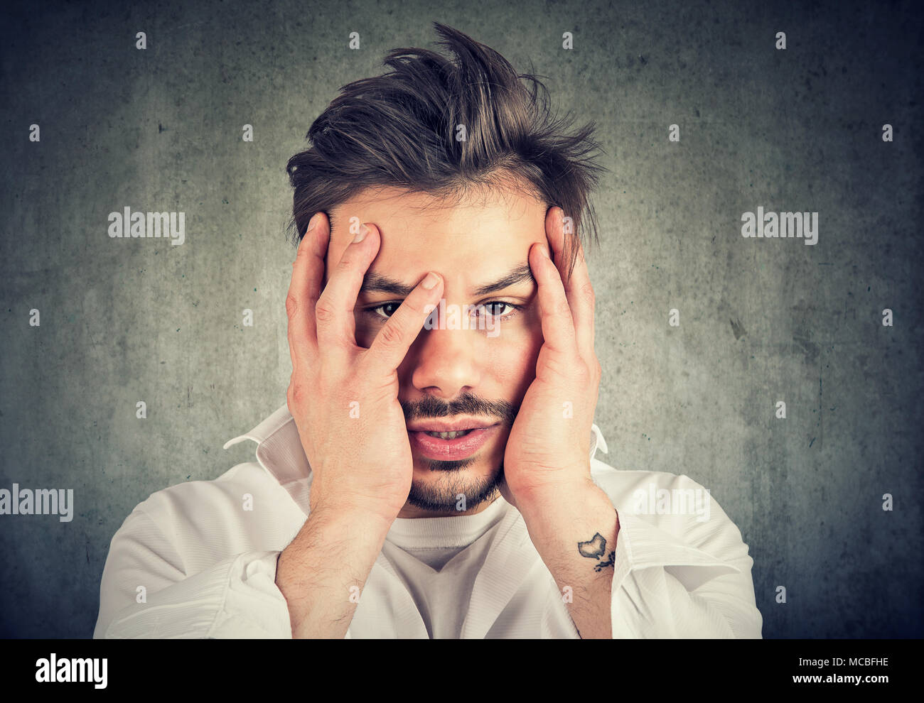 Miserable guy having a big problem and covering face dramatically looking at camera. - Stock Image