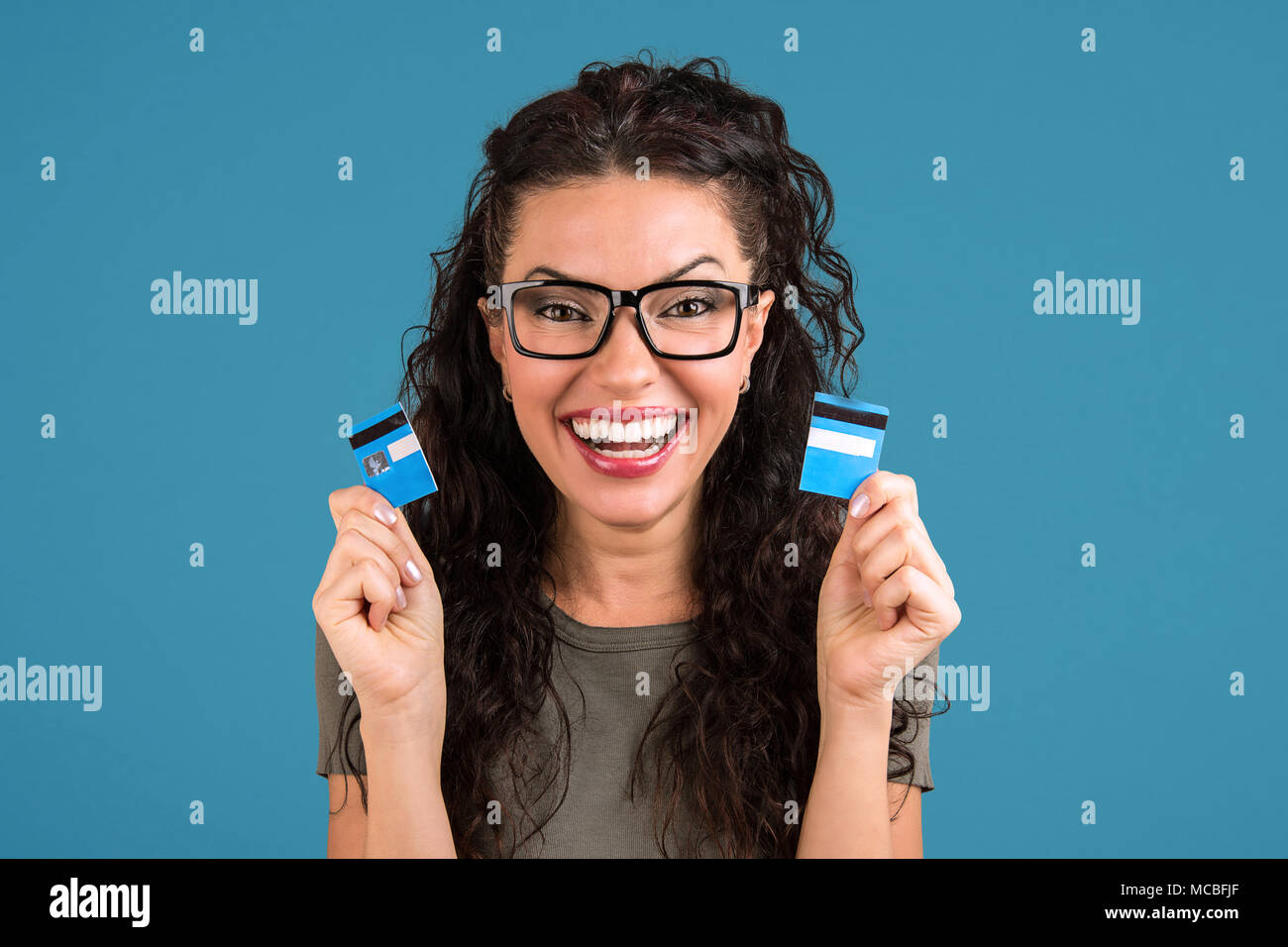 Happy debt free woman in glasses holding a credit card cut in two pieces - Stock Image
