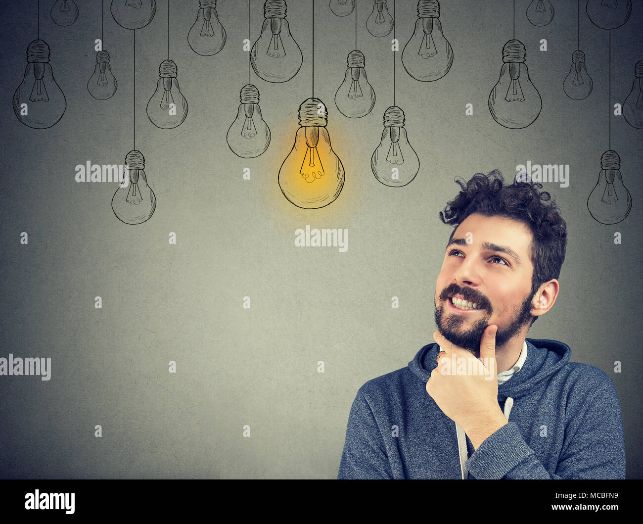 Portrait of a thinking man smiling looking up at light idea bulb above head isolated on gray wall background - Stock Image