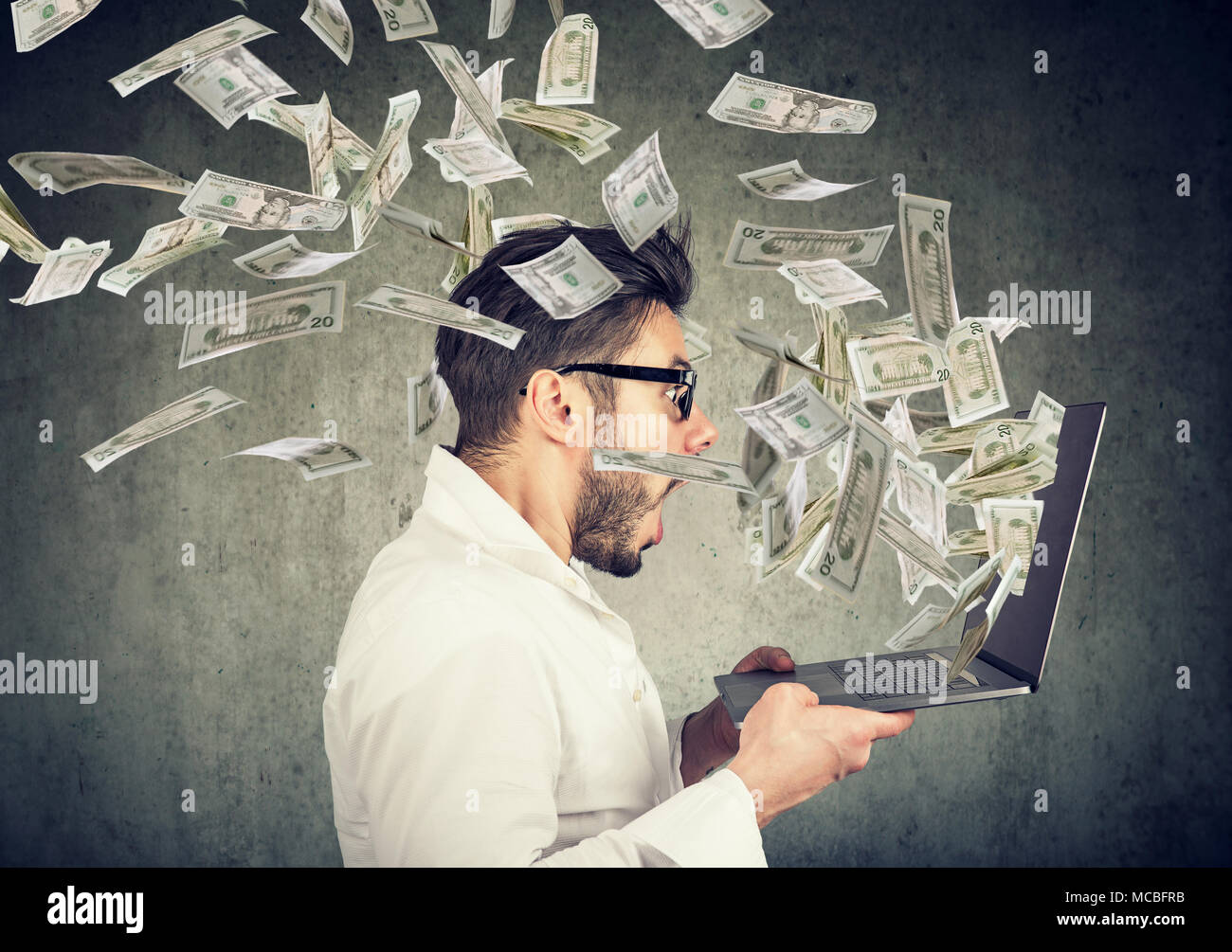 Side view of man holding laptop and winning plenty of money in social media. - Stock Image