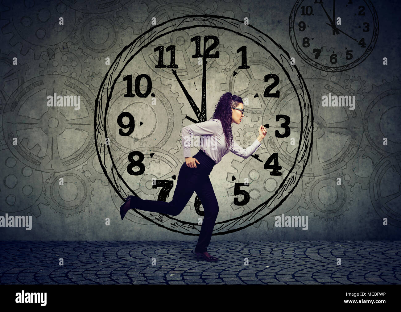 Young business woman running out of time - Stock Image