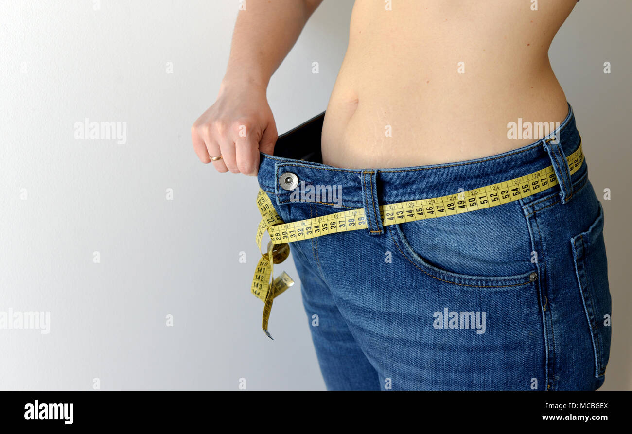 Weight loss concept. Woman shows her weight loss by wearing an old jeans. Healthy lifestyle, dieting concept with oversized jeans. - Stock Image