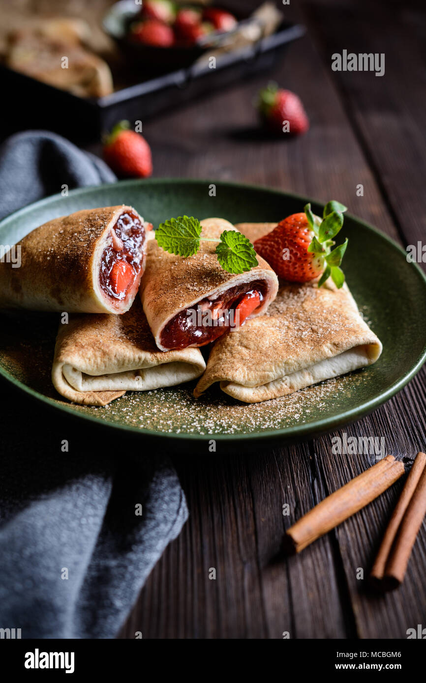 Sweet baked Chimichangas with strawberry filling and cinnamon sugar icing - Stock Image