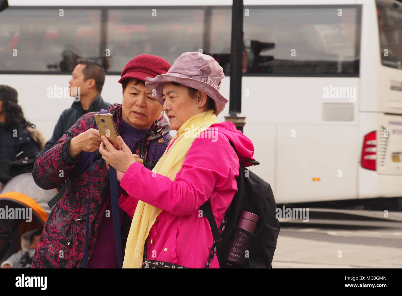 Two older women looking at a smartphone in Trafalgar Square, London one wearing a bright pink coat and hat and a white coach in the background - Stock Image