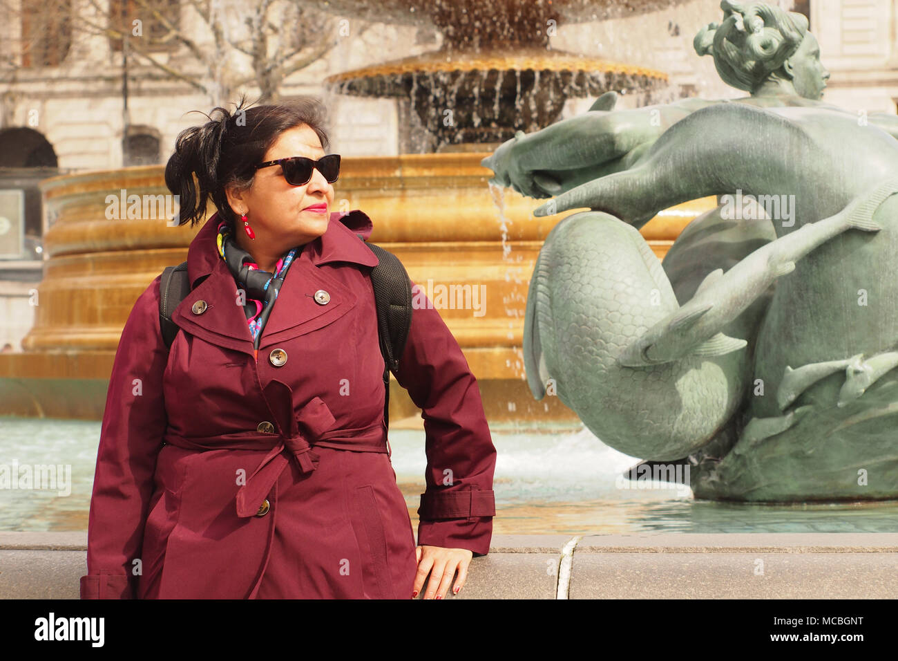 A woman sightseer in Trafalgar Square, London, taking in the sights on a bright winters day by the fountains - Stock Image