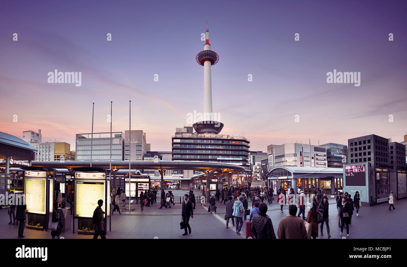 Kyoto Station busy with people in the evening with Kyoto tower and Kyoto tower hotel beautiful sunset city scenery in Stock Photo