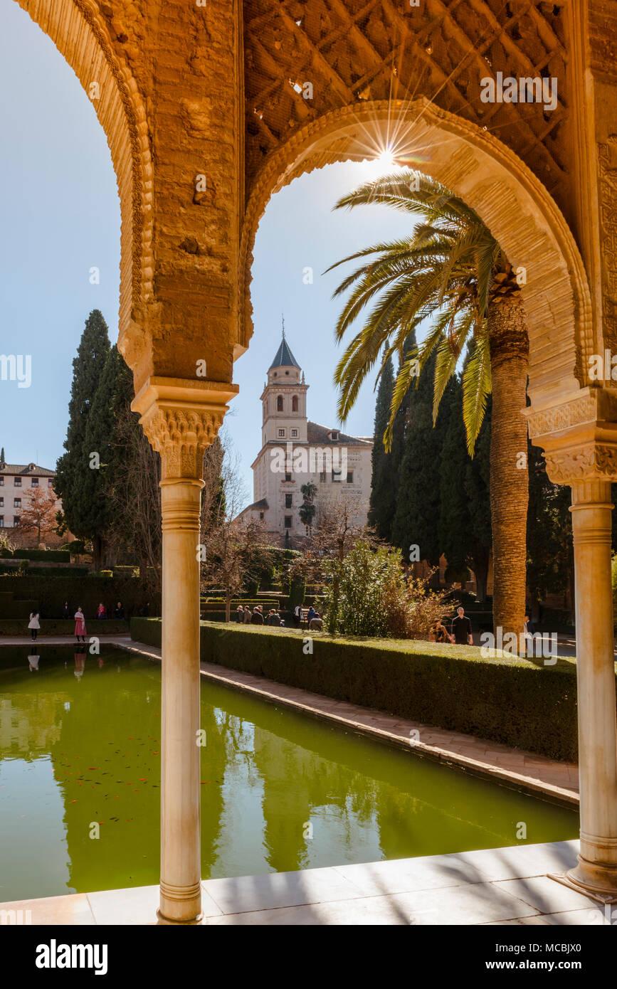 View through a arcade, Church of Santa María de la Alhambra, El Partal with pool and palm trees, Alhambra - Stock Image