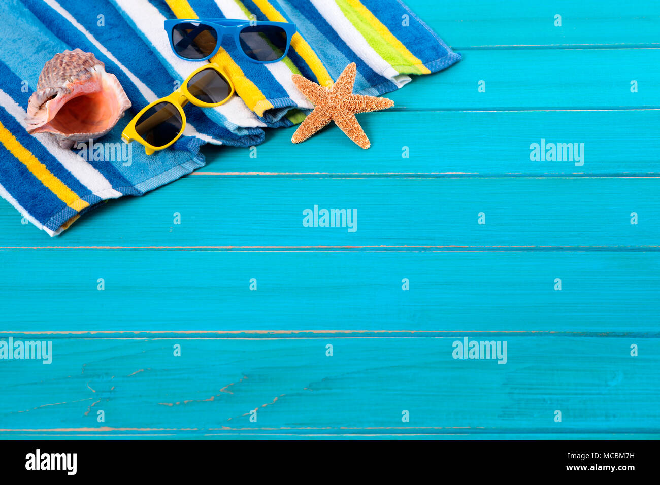 Beach scene with striped towel, sunglasses, starfish and ...