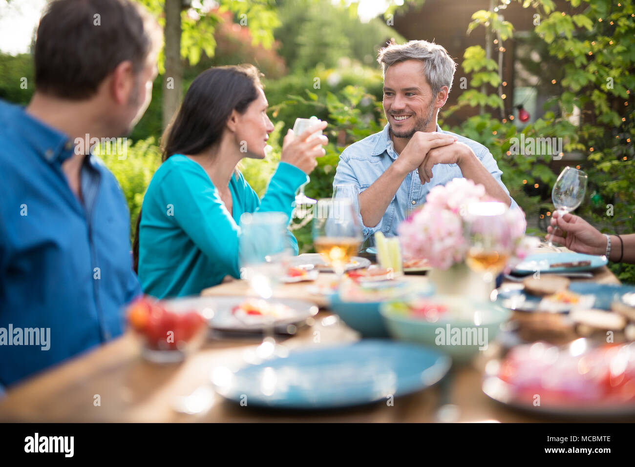 Group of friends gathered around a table in a garden on a summer evening to share a meal and have a good time together - Stock Image