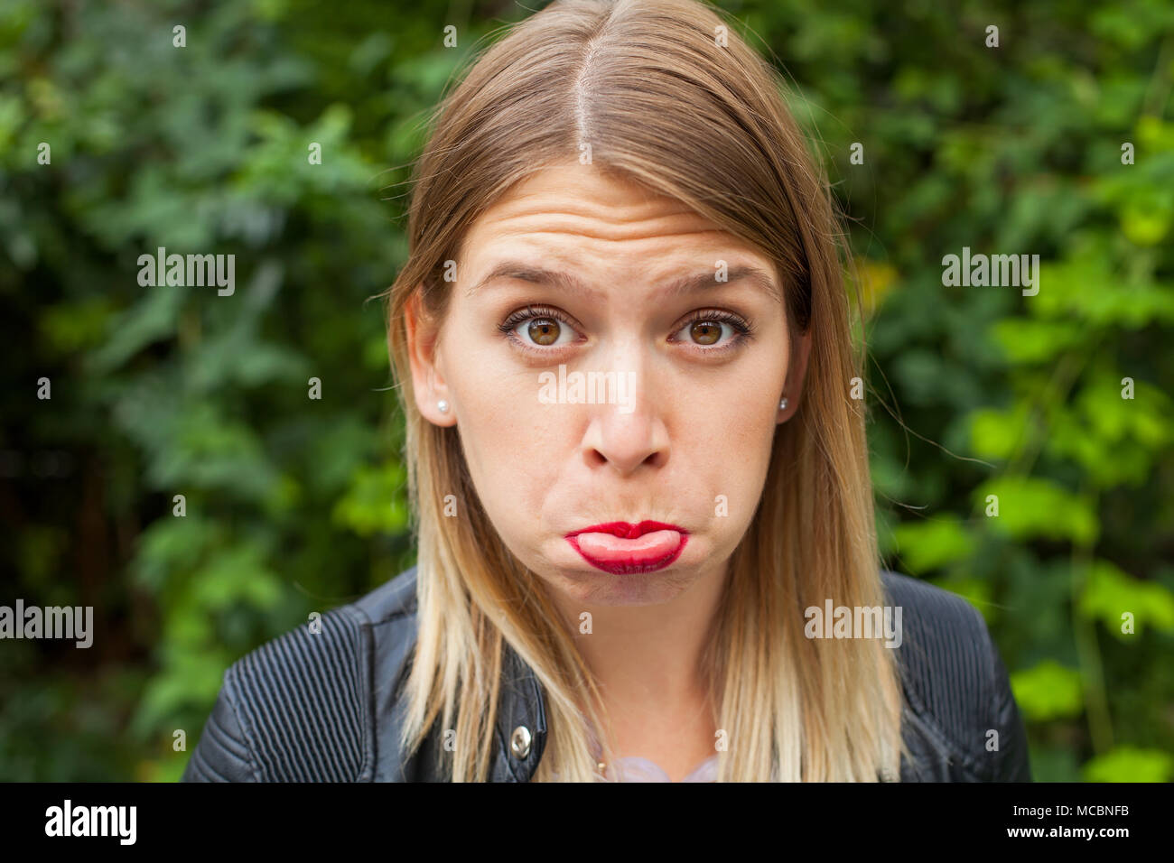 Young woman making a grimace outdoor, green background. Sad - grumpy expression - Stock Image