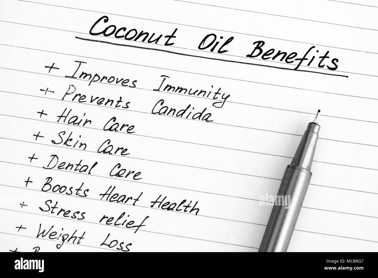 List of Coconut Oil Benefits with pen. Close-up. - Stock Image