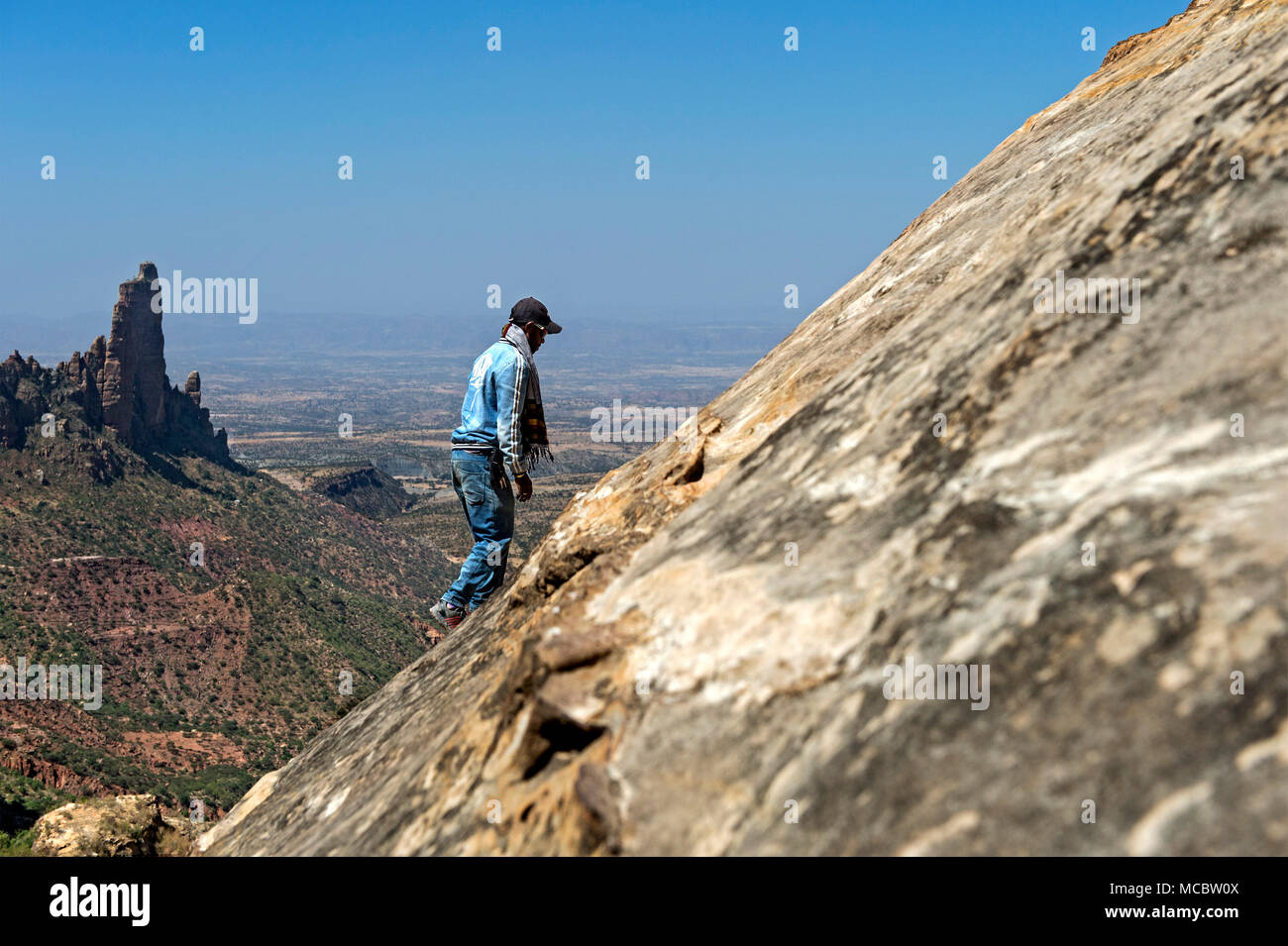 Local man on the exposed ascent to the rock-hewn churches Maryam and Daniel Korkor, the Koraro spires of Abuna Yeamta Guh church behind, Ethiopia - Stock Image