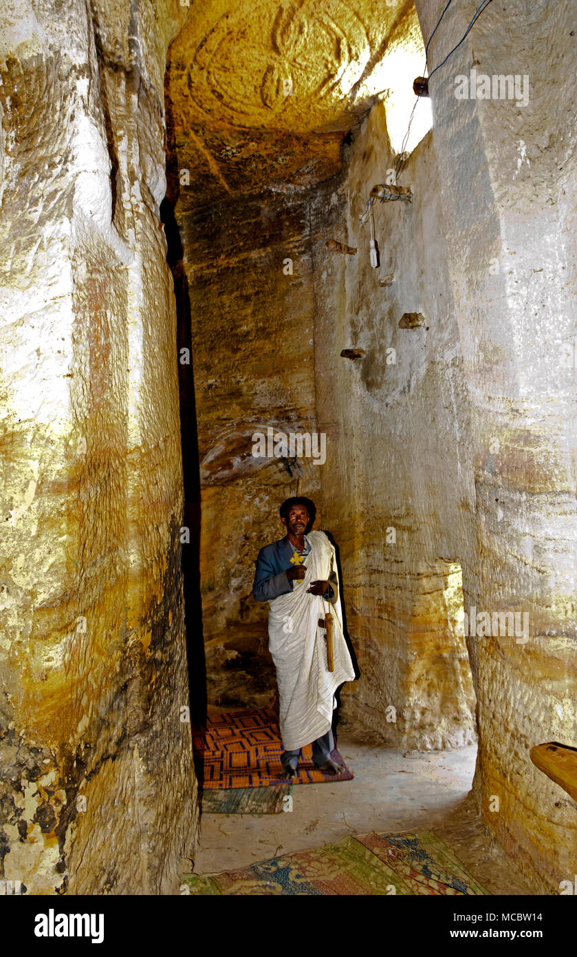 Orthodox priest standing inside a rock corridor in the rock-hewn church Medhane Alem, Tigray region, Ethiopia - Stock Image