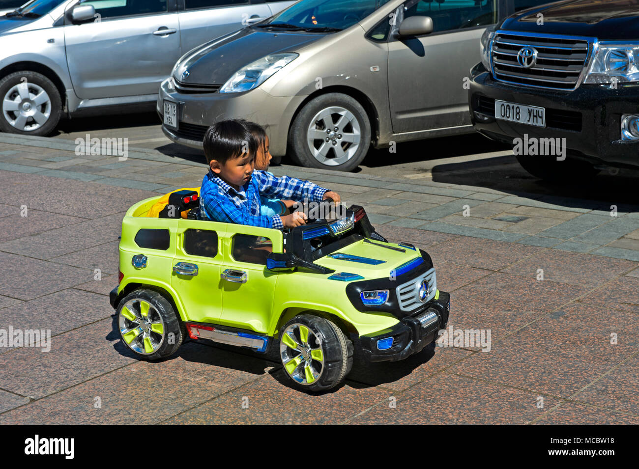 Looking for a parking space, kids riding an electric toy cars, Ulaanbaatar, Mongolia - Stock Image