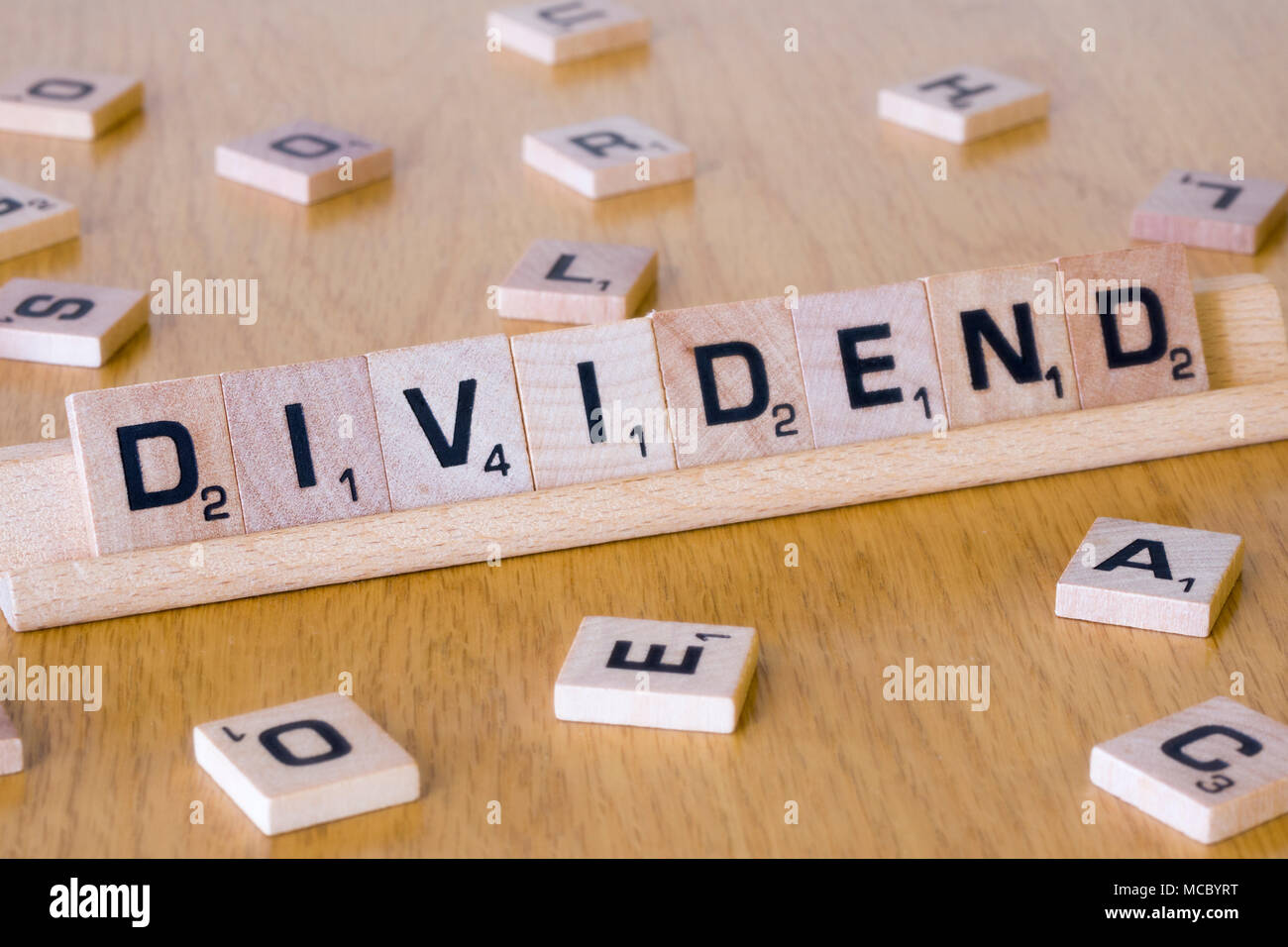 Scrabble letters spelling out the word Dividend - Stock Image