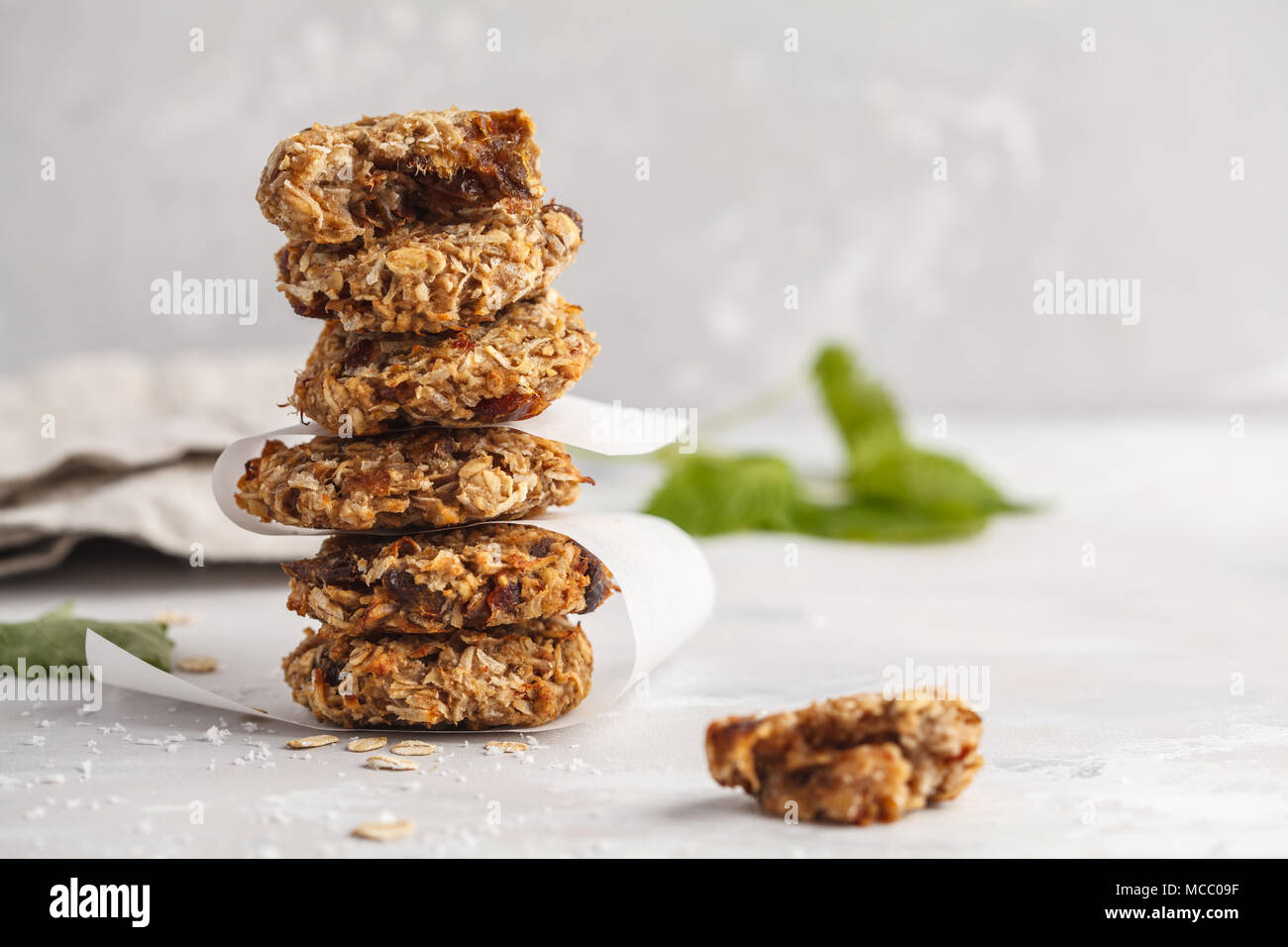 Vegan oatmeal cookies with dates and a banana. Healthy vegan detox dessert on a light background - Stock Image