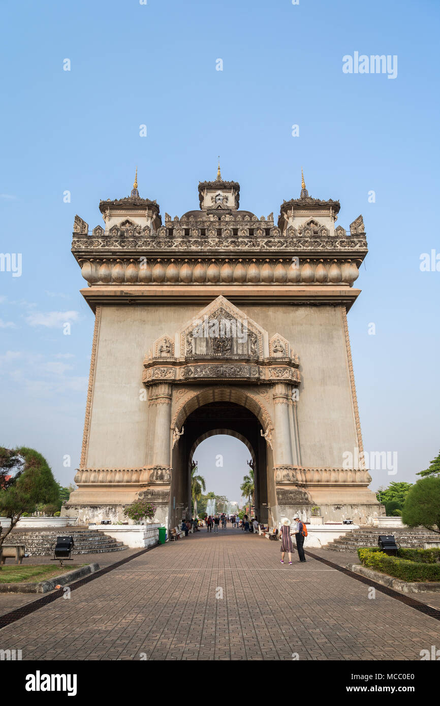 Tourists at the Patuxai (Victory Gate or Gate of Triumph) war monument in Vientiane, Laos, on a sunny day. - Stock Image