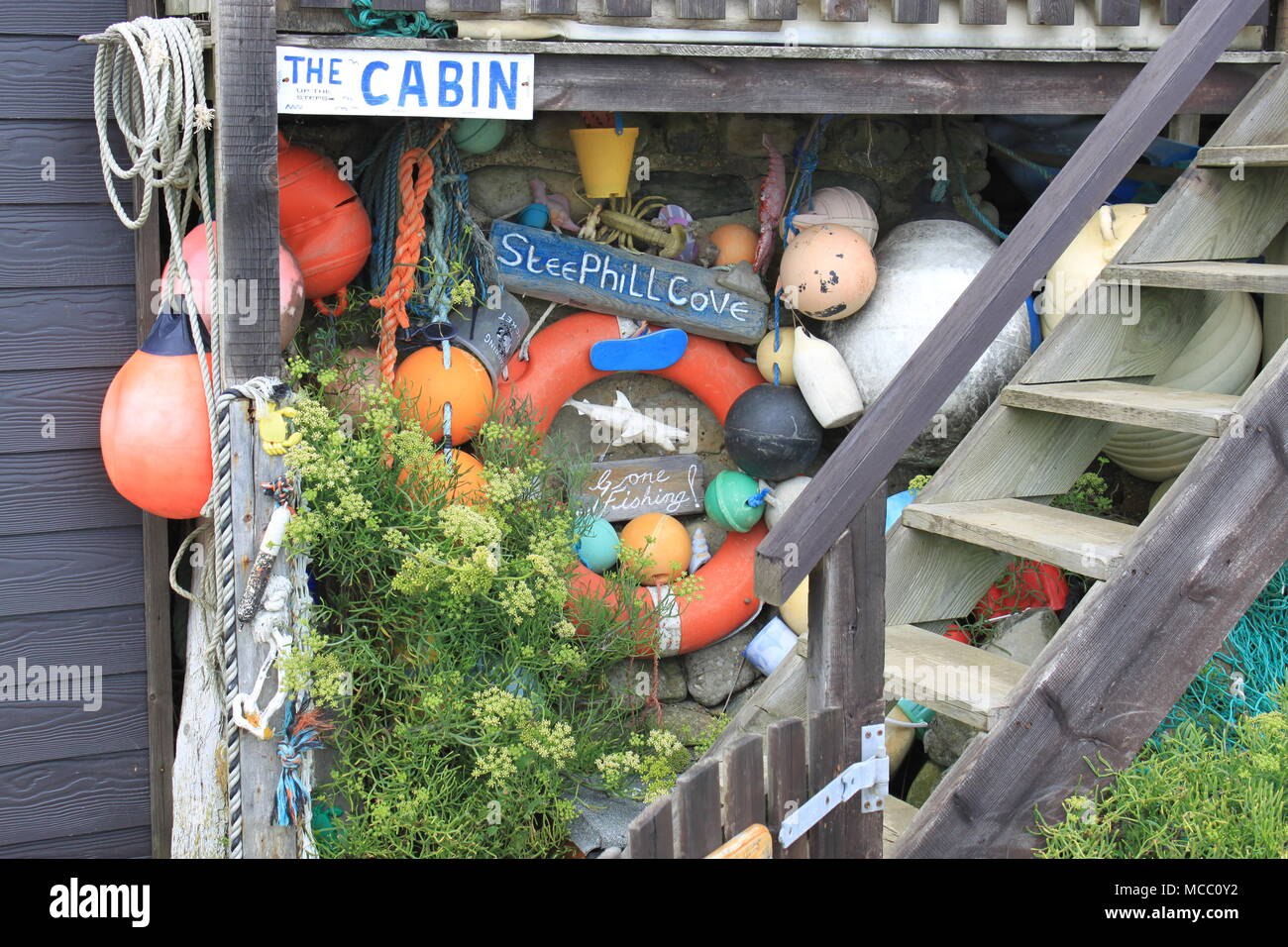 Collection of colourful flotsam and jetsam hanging on a wooden cabin in Steephill Cove, Ventnor, Isle of Wight, England, UK, PETER GRANT - Stock Image