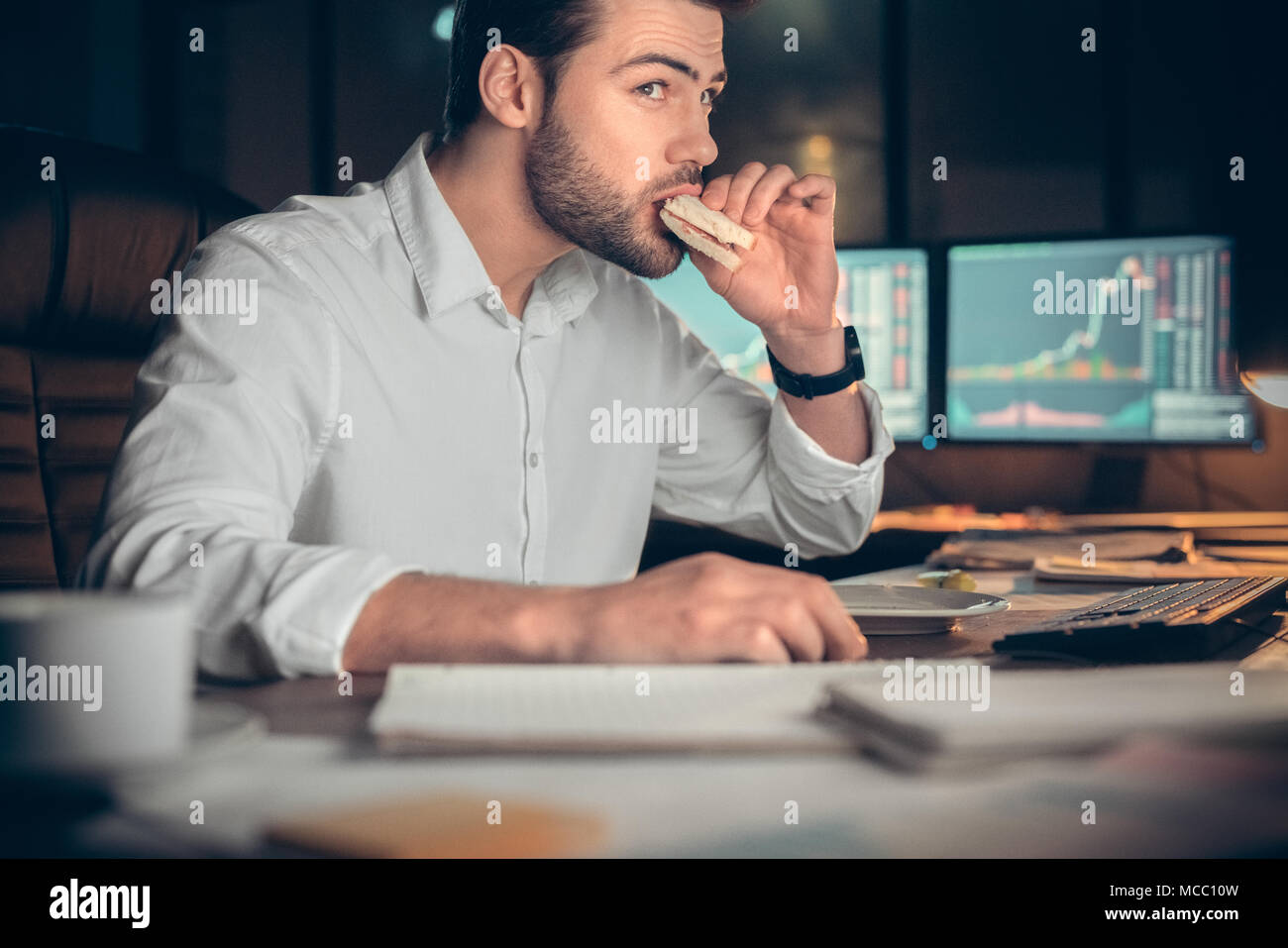 Busy businessman having late lunch eating sandwich in office working at night, stock broker trading online and eating snack looking at computer, workp - Stock Image