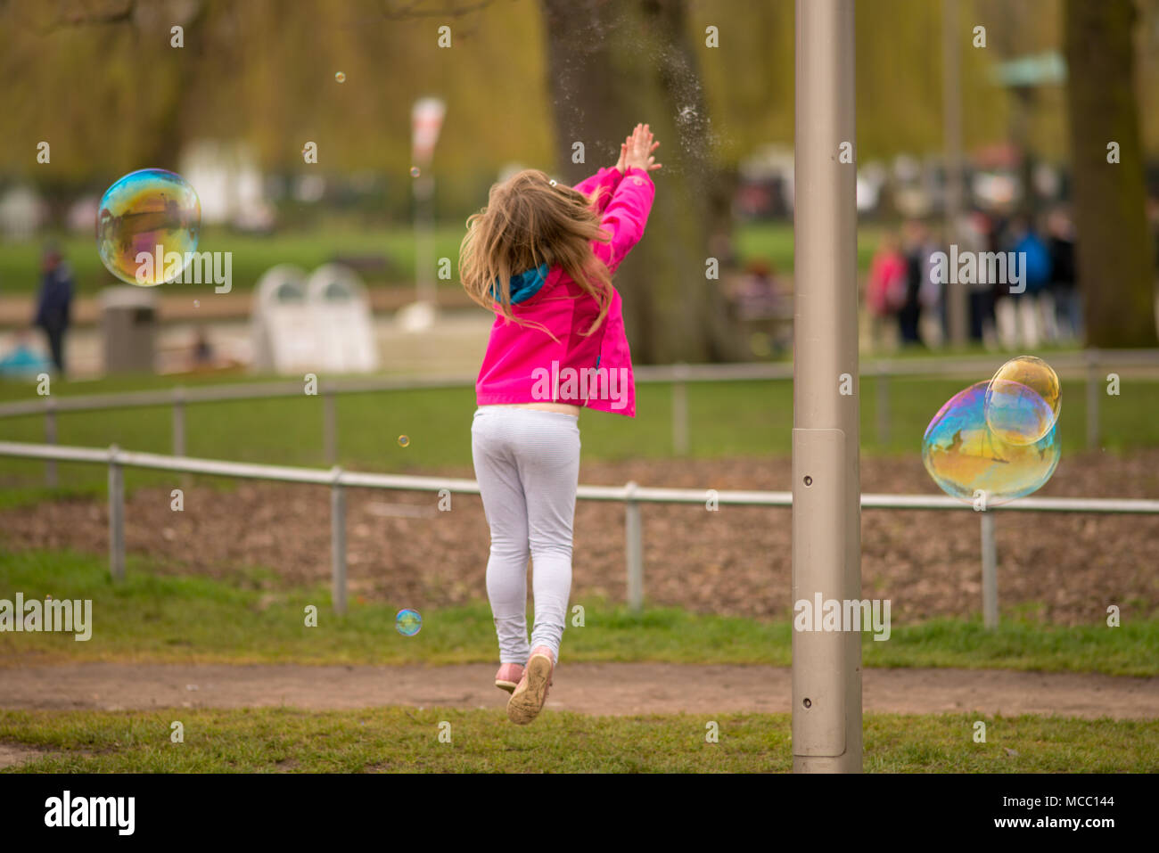 Young child jumps in the air and bursts a soap bubble caught at the exact moment it explodes - Stock Image