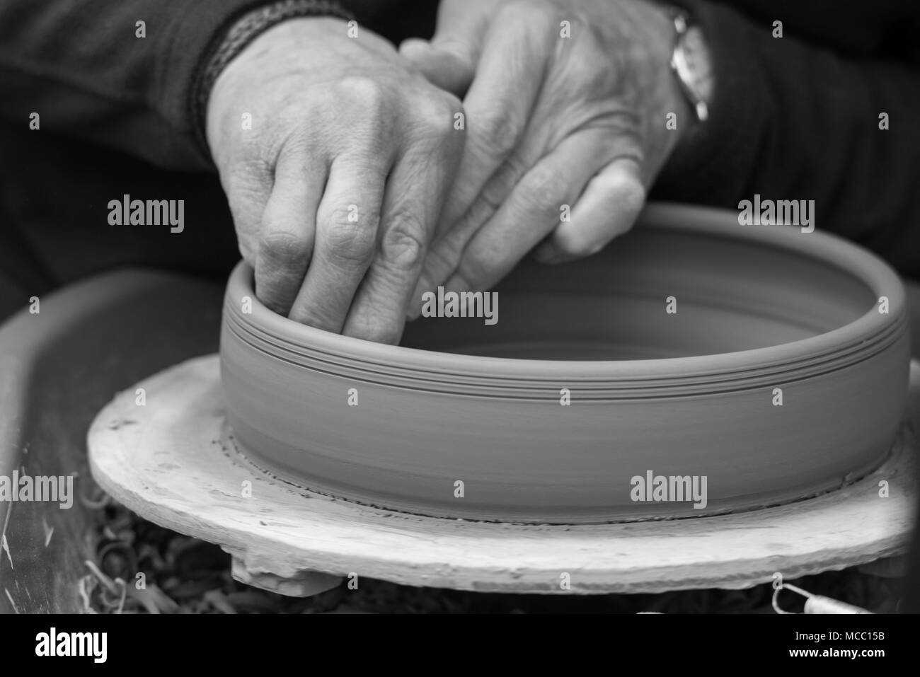 artisan potter makes earthenware pot on wheel using various tools - Stock Image