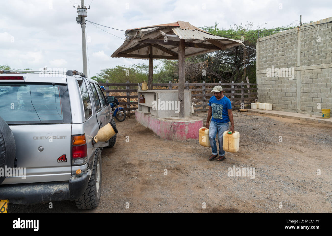 A man carries two jugs of gasoline to fill up a car in a rural petro station. Colombia, South America. - Stock Image