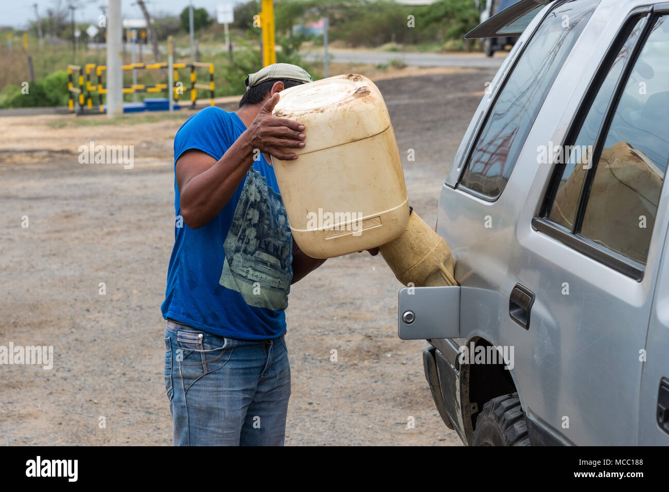 A man fills up gasoline for a car in a rural petro station. Colombia, South America. - Stock Image