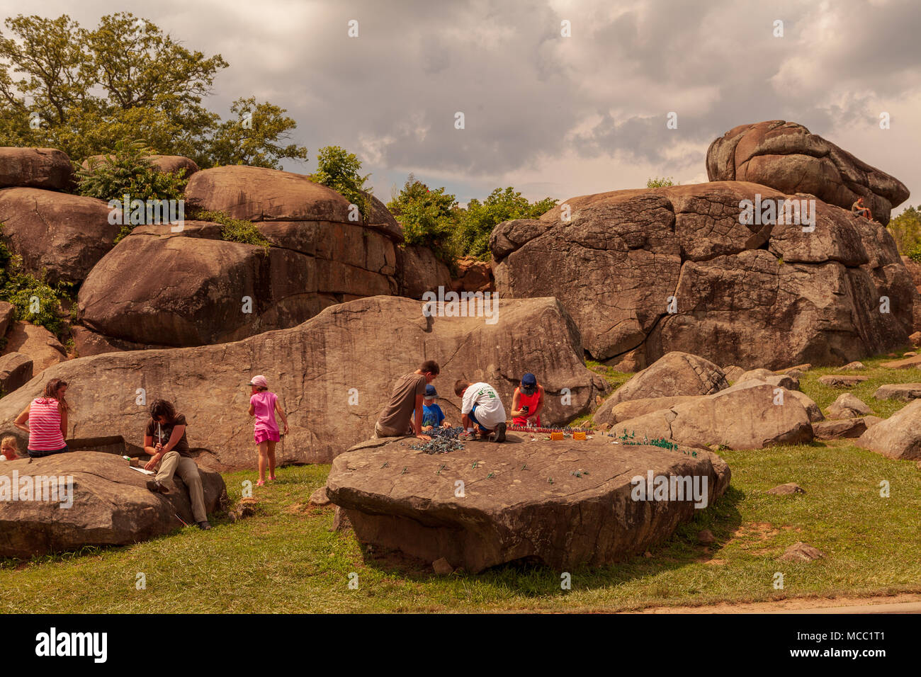 Gettysburg, PA, USA - July 8, 2013:  Visitors at Devil's Den on the Gettysburg Battlefield lounge on boulders used artillery and infantry on day two o Stock Photo