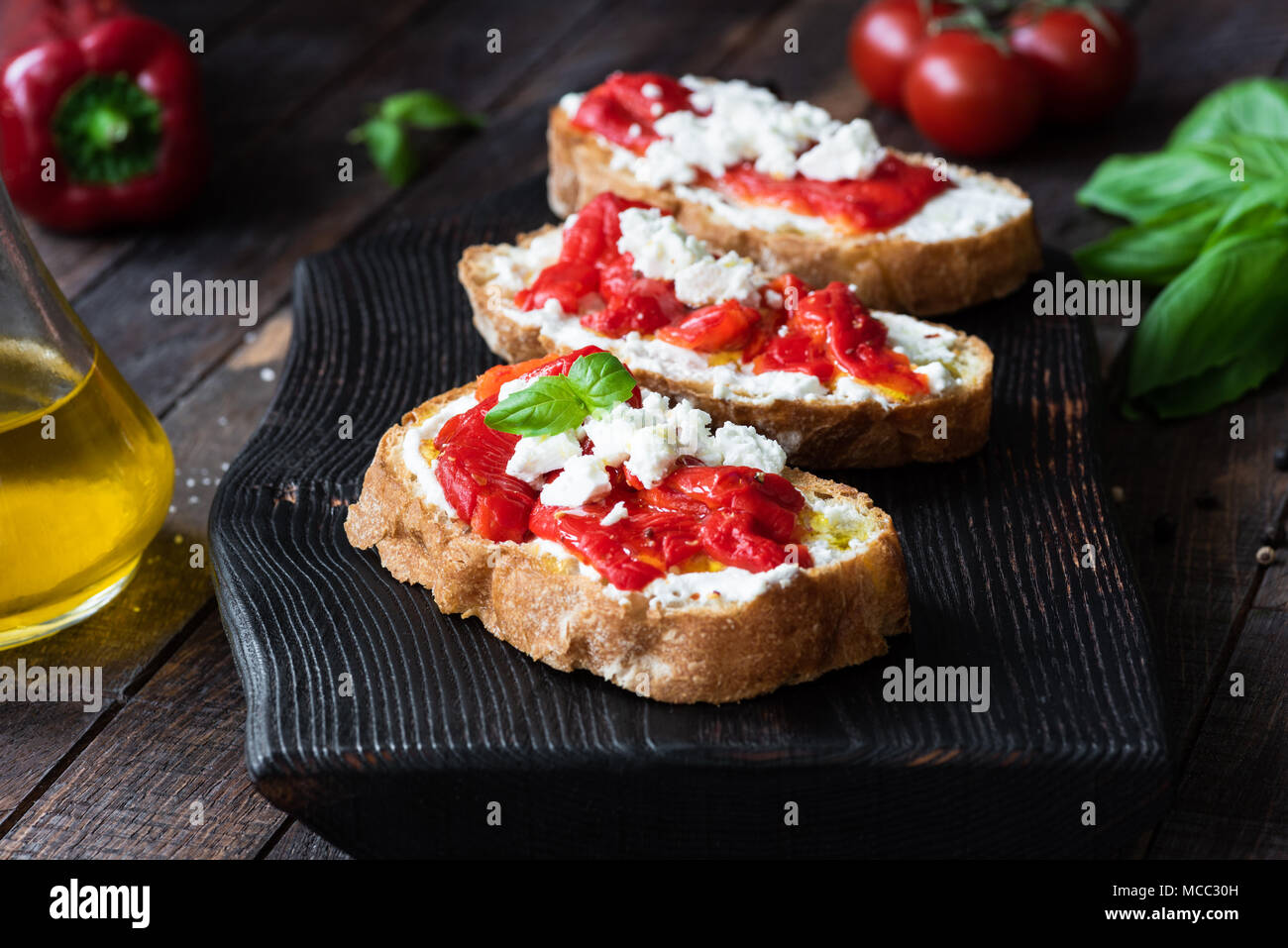 Bruschetta with roasted pepper and goat cheese on black cutting board. Closeup view, selective focus - Stock Image