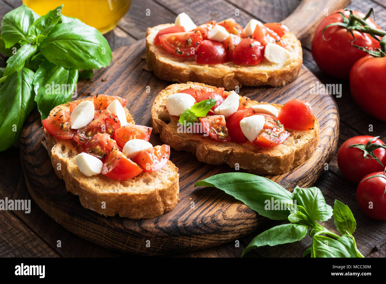 Bruschetta with tomato, basil and mozzarella cheese on wooden board. Traditional italian appetizer or snack, antipasto - Stock Image