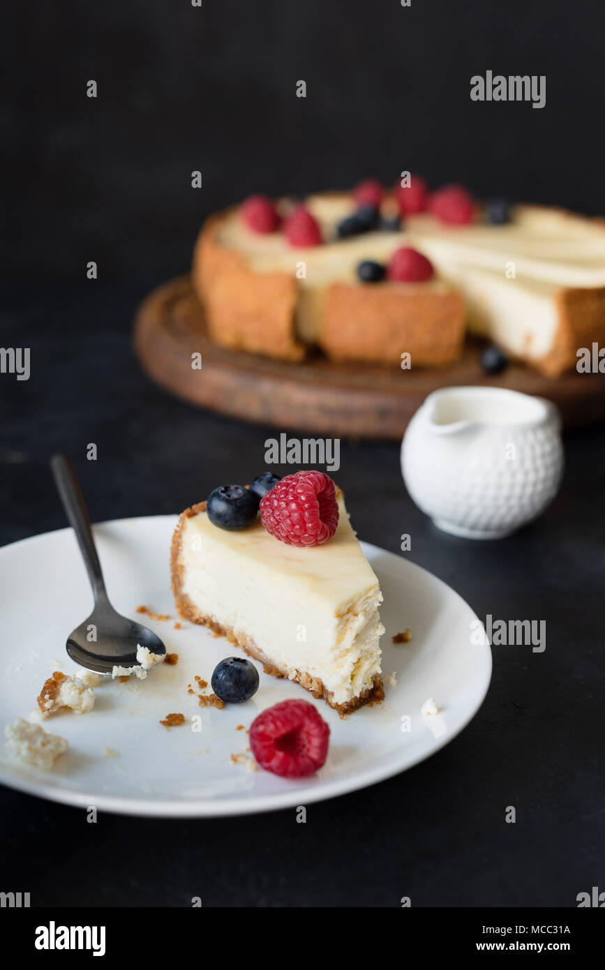 Slice of cheesecake with missing bite on white plate. selective focus - Stock Image
