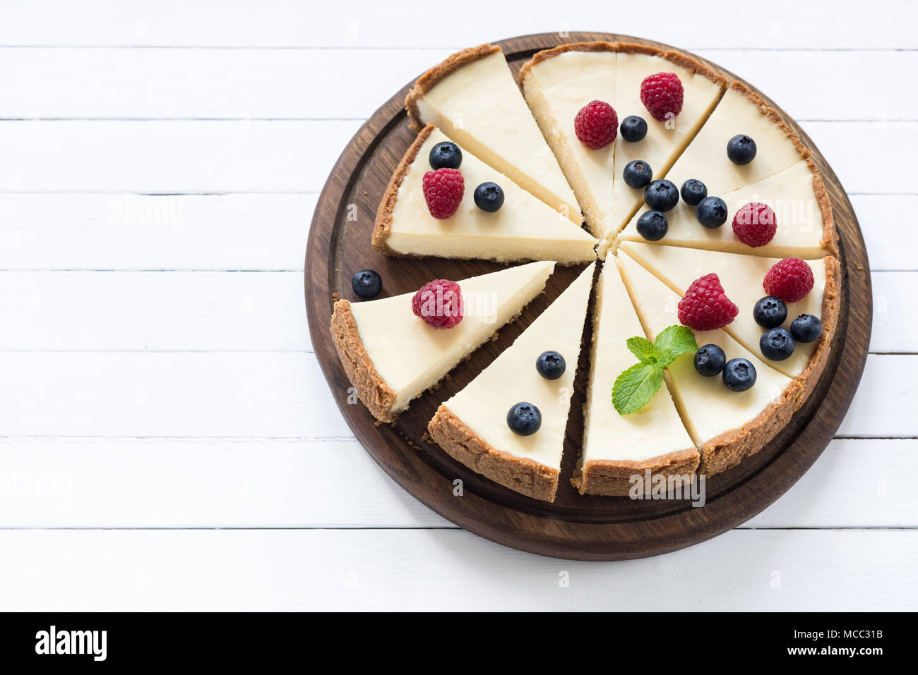 Cheesecake with summer berries cut into pieces on white background. Top view with copy space for text Stock Photo