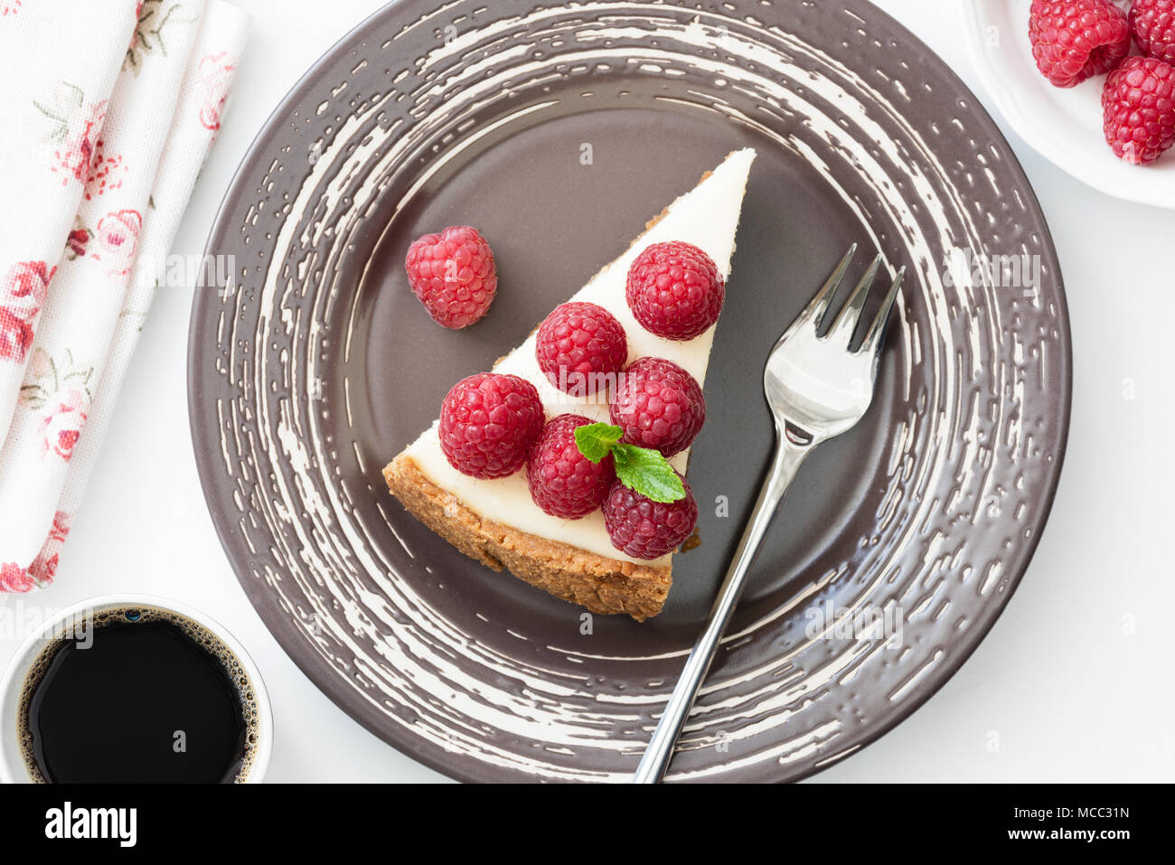 Top view of cheesecake slice with fresh raspberries on white background, selective focus - Stock Image