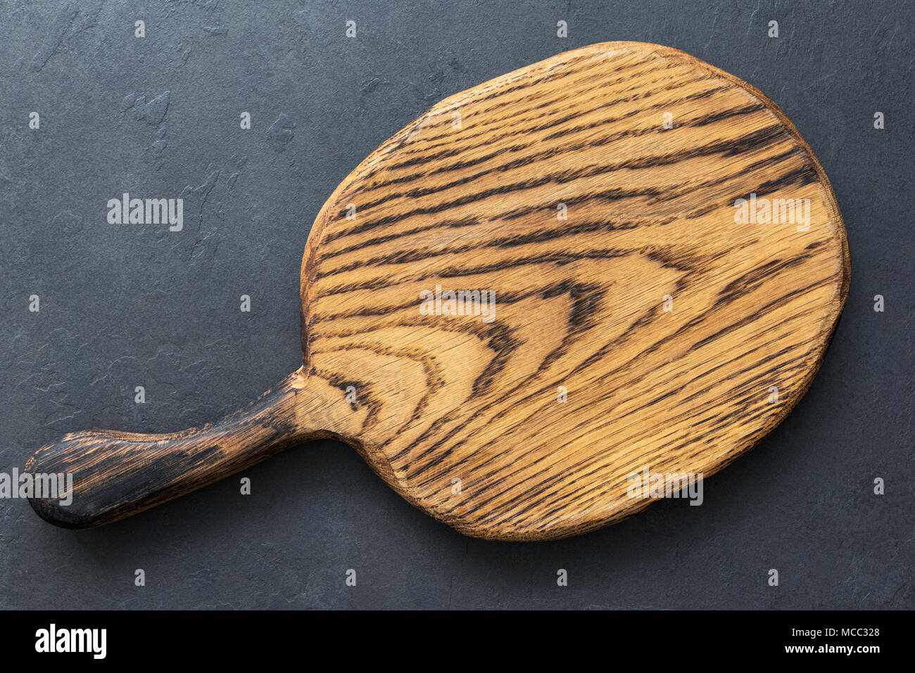 Wooden cutting board on slate background, top view with copy space for text. Horizontal composition - Stock Image