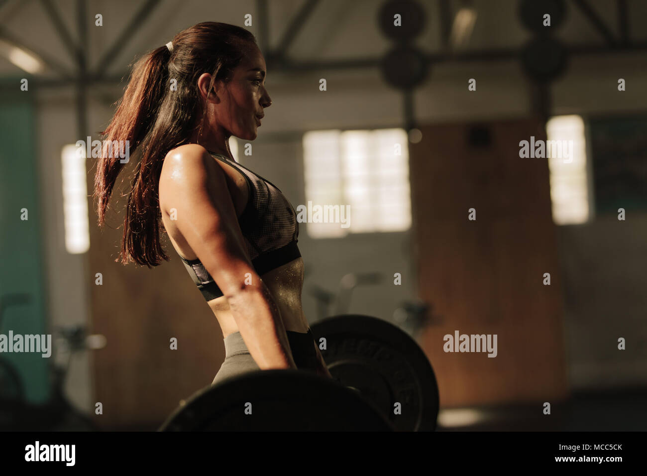 Physically fit woman lifting heavy weights. Fitness female doing heavy weight workout at gym. - Stock Image