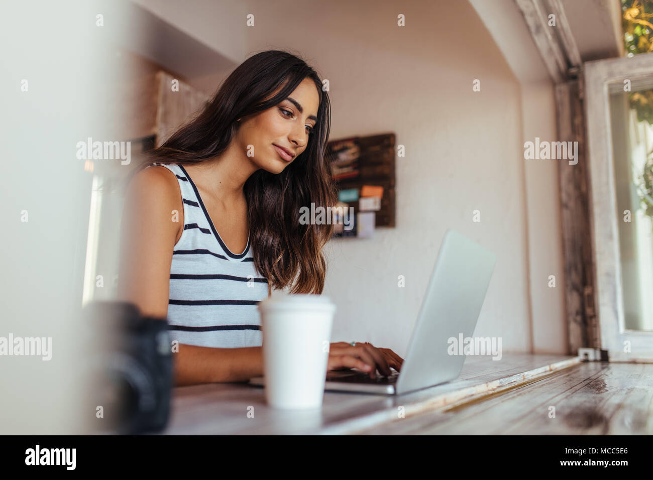 Woman blogger using laptop at home. Woman sitting with coffee glass and camera on the table working on her laptop computer. - Stock Image