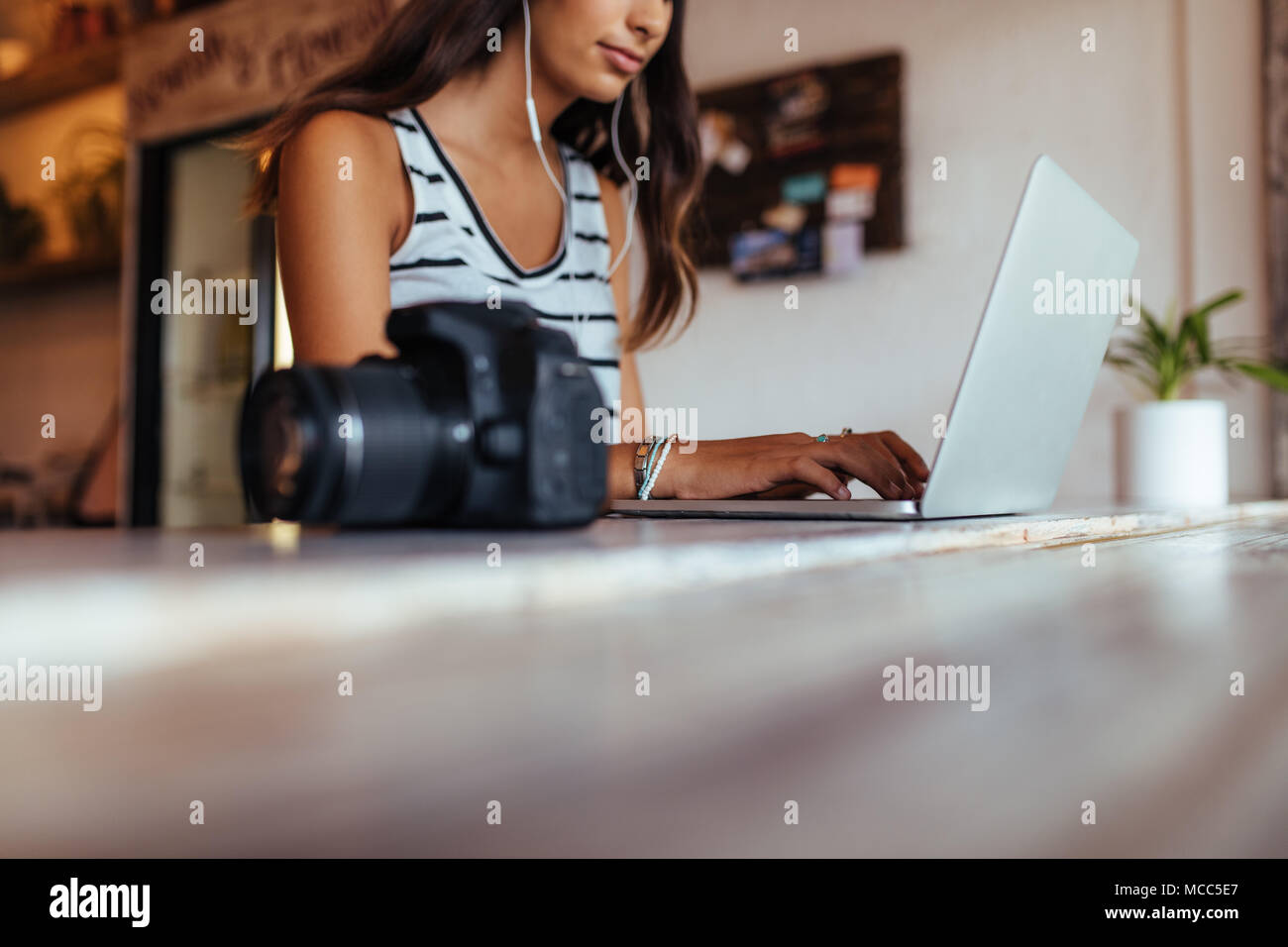 Woman blogger using laptop at home wearing earphones. Woman sitting with DSLR camera on the table working on her laptop computer. - Stock Image