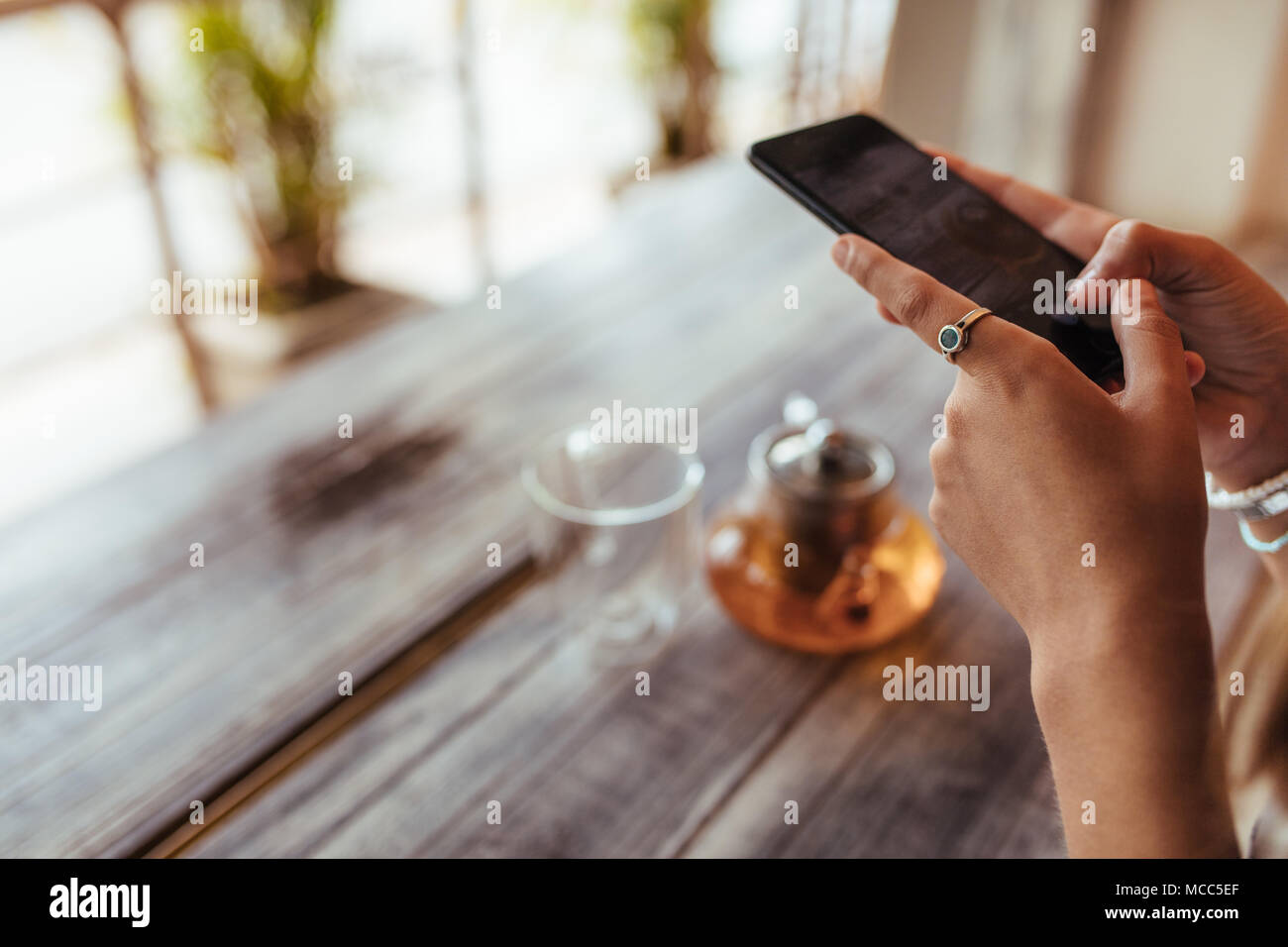 Close up of a woman capturing photos of a glass teapot and an empty glass using a mobile phone for her food blog. Food blogger taking a photo for her  - Stock Image