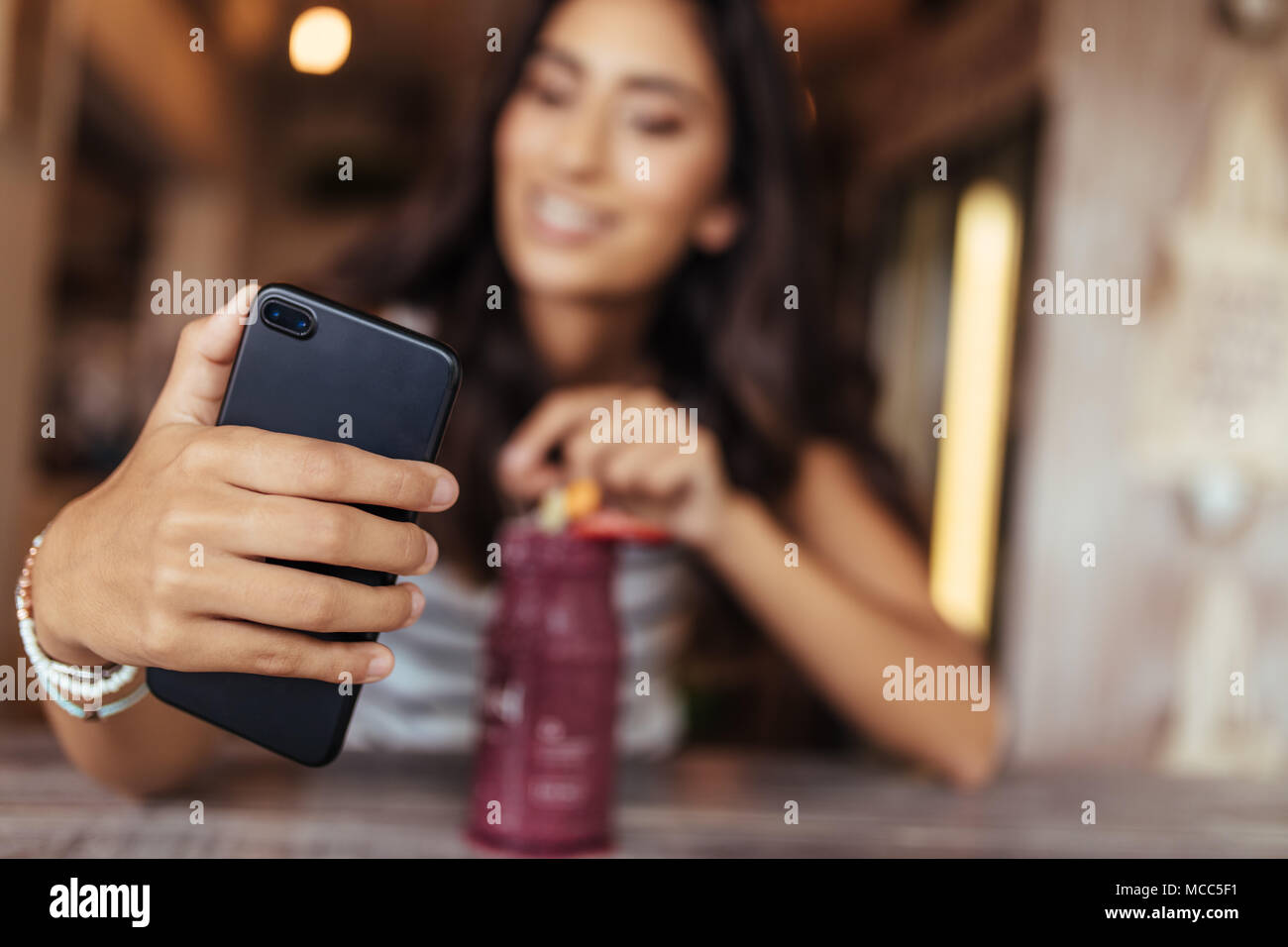 Woman taking a selfie with a smoothie placed on the table using a mobile phone for her food blog. Food blogger shooting photos for her blog at home. - Stock Image