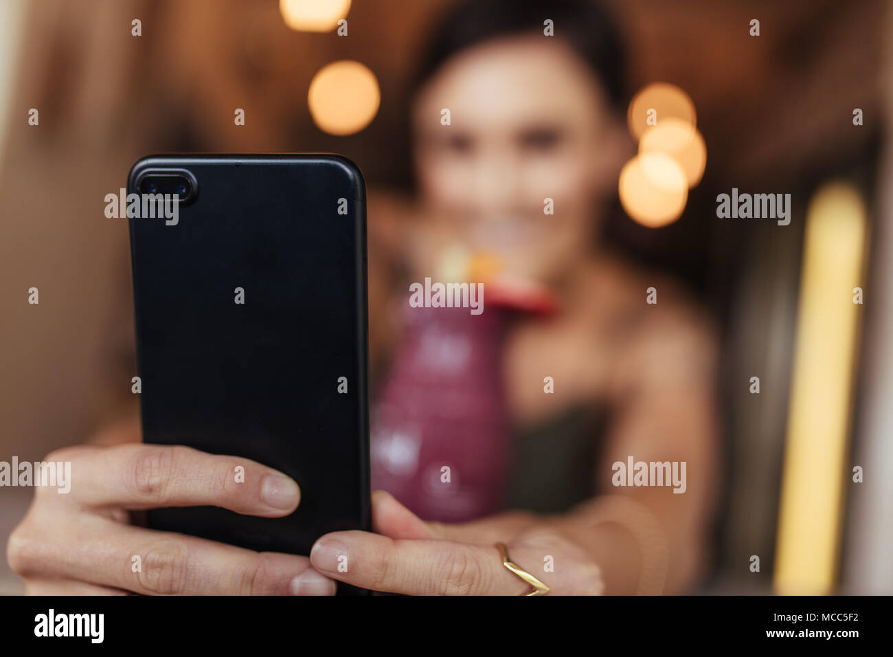 Blurred image of a woman taking a selfie with a smoothie placed on the table using a mobile phone. Food blogger shooting photos for her blog at home. - Stock Image