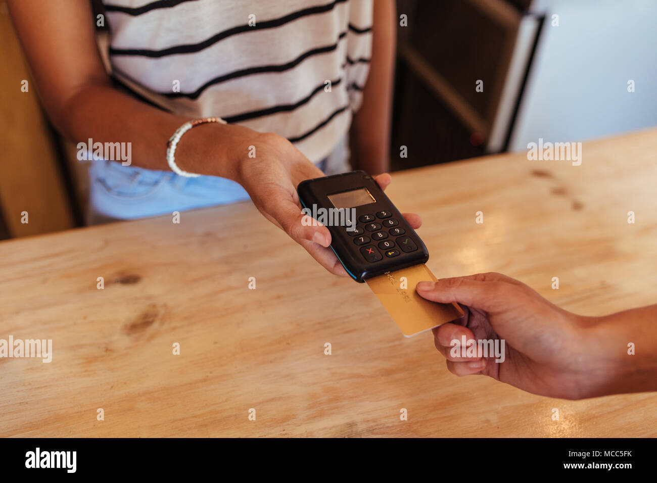 Woman entrepreneur using a wireless point of sale machine to effect a cashless payment. Close up of a woman holding a wireless point of sale machine w - Stock Image
