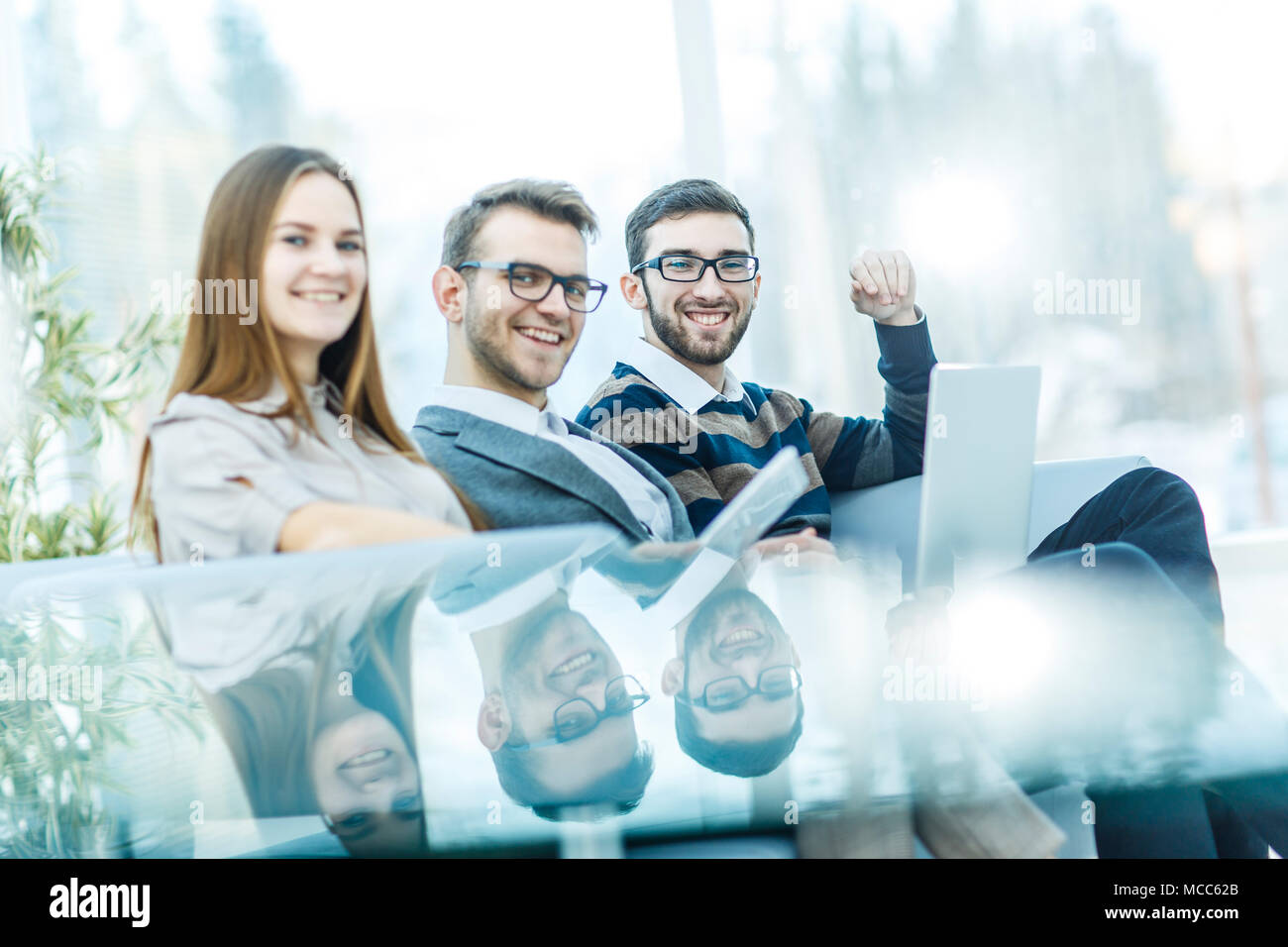 employees with a laptop sitting in the lobby of the office - Stock Image
