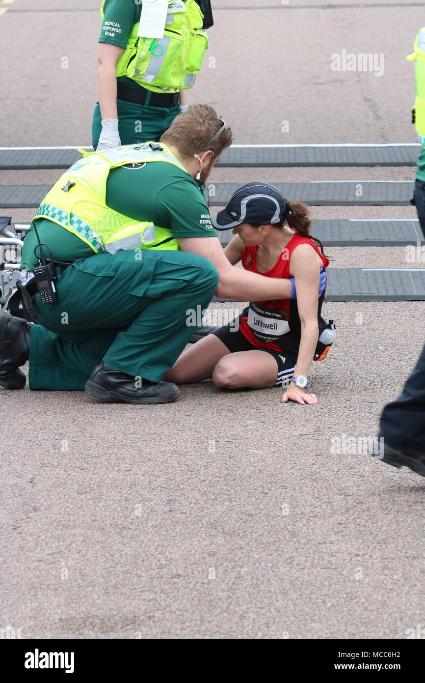a paramedic helps a female runner who has collapsed at the finish line after completing a marathon - Stock Image
