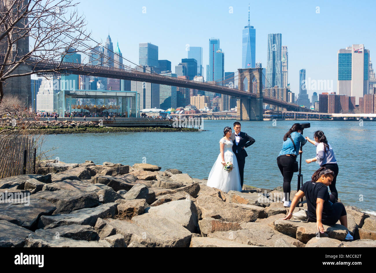 An Asian couple having wedding video done in DUMBO Brooklyn, with the Brooklyn Bridge, Jane's Carousel and Manhattan skyline in the background - Stock Image