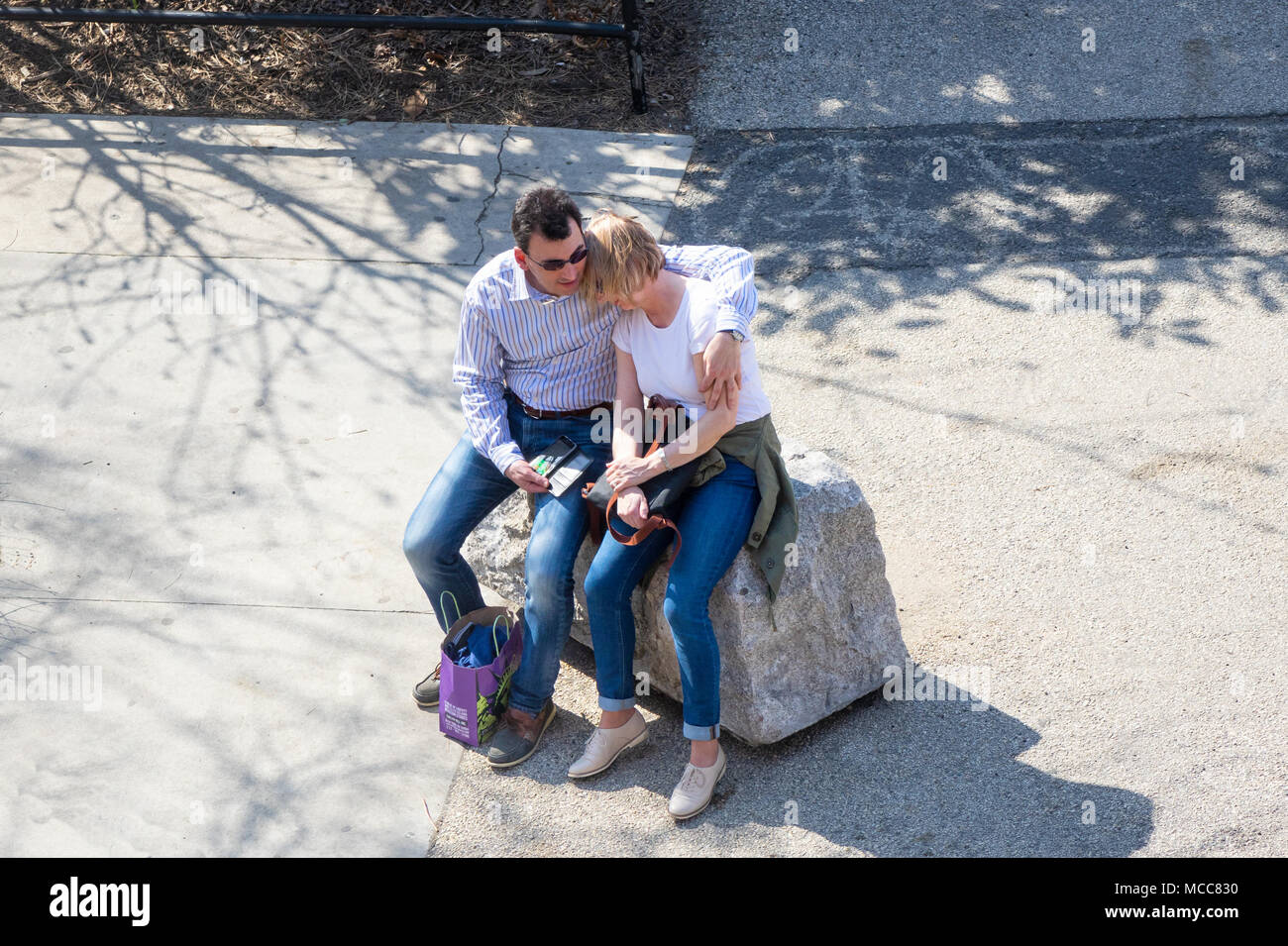 A tourist couple having a quiet and tender moment on a mild weather day in NYC - Stock Image