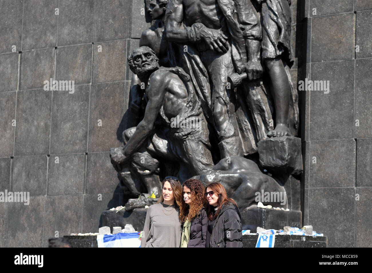 Warsaw Poland Visitors at the Monument to the Ghetto Heroes of the Warsaw Ghetto Uprising - Stock Image