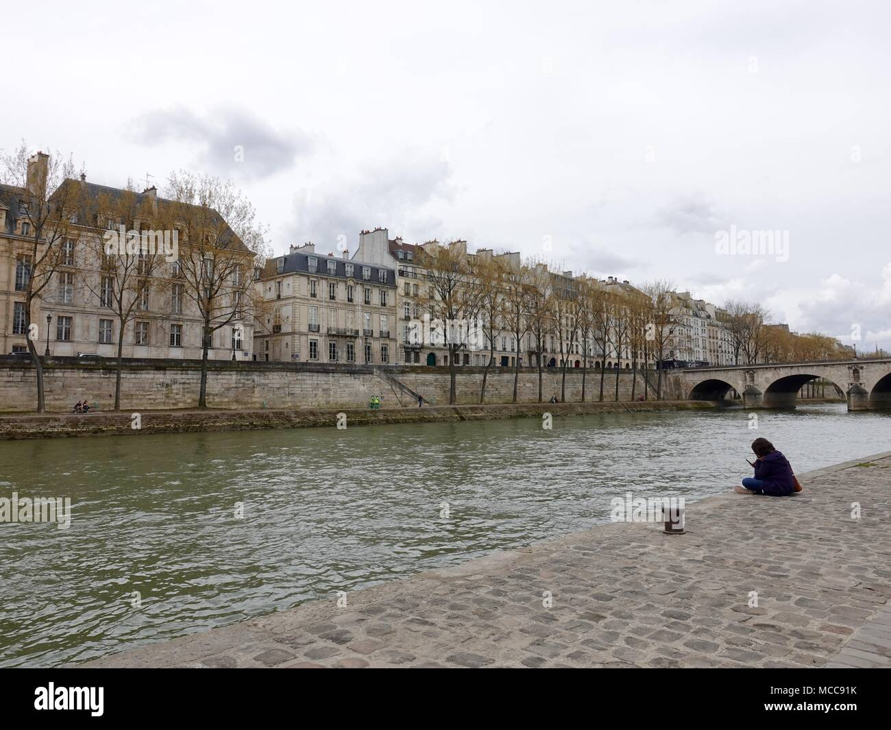 Solitary woman sits along the bank of the Seine River in the Parc Rives de Seine, looking across at Ile Saint-Louis. Paris, France. - Stock Image