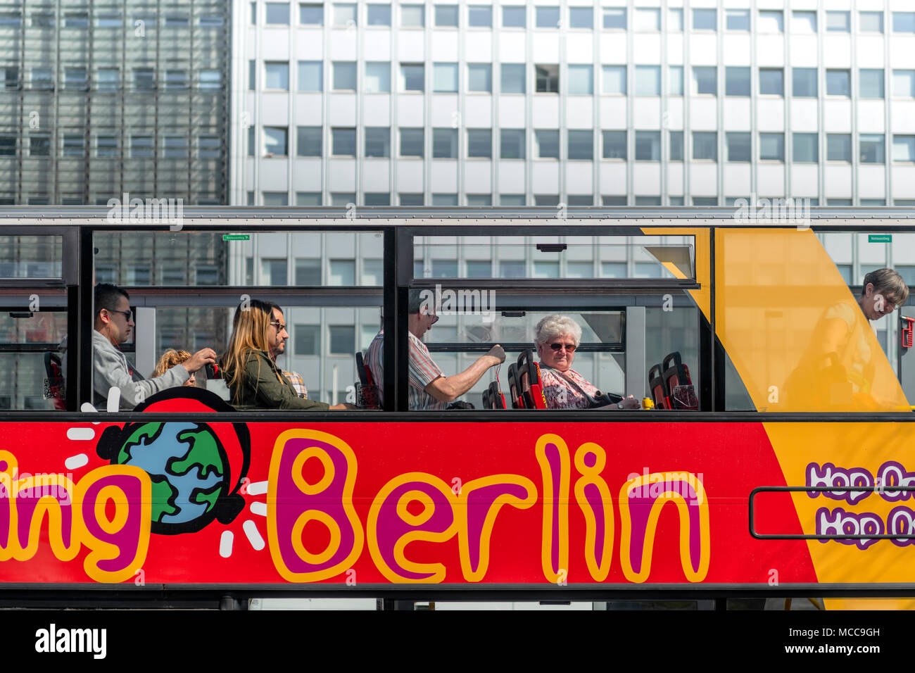 People sit on the top deck of one of the many 'Hop On, Hop Off' buses that are a major tourist attraction in the German capital of Berlin. - Stock Image