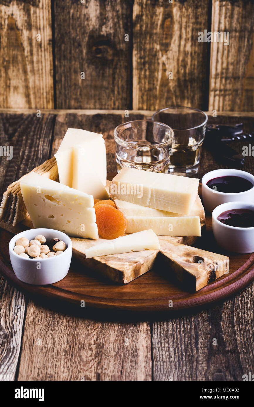 Cheese platter, fruit jam, nuts and wine on wooden cutting board, delicious holiday appetizer - Stock Image