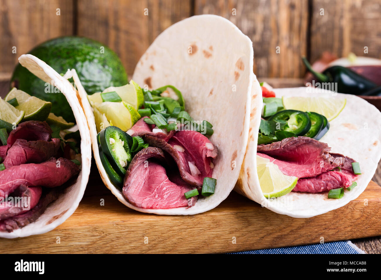 Tacos with beef steak and vegetables on wheat flour tortillas, Mexican style meal - Stock Image